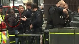The suspect is taken away by police.