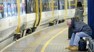 Commuters wait for a train