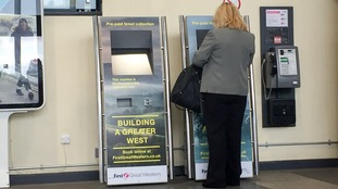 A woman uses a ticket machine.