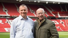 Manchester United legend Sir Bobby Charlton with Stuart Hughes who was injured by a landmine whilst on assignment with BBC News