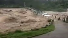 Drivers risk their lives in perilous flooded bridge crossing
