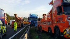 Three lanes were closed on the M1 after a lorry became stuck on the central reservation.