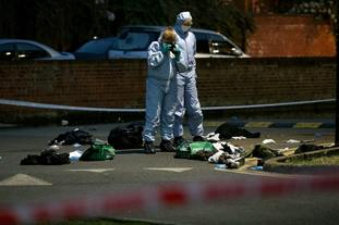 Forensics officers inspect the scene on Thursday evening.