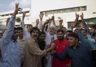 Supporters of Imran Khan celebrate outside the National Assembly