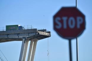A green truck on the bridge.