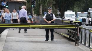 A police officer stands at a Westminster crash barrier.