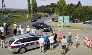 People watch the arrival of Vladimir Putin's convoy