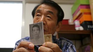 South Korean Lee Soo-nam, 76, shows photos of his brother Ri Jong Song.