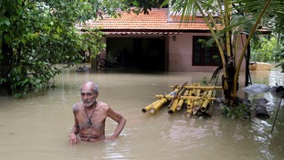 An elderly man wades through flood waters.