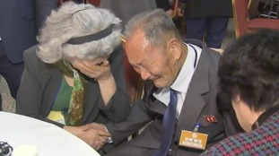 Two Koreans cry as they meet for the first time in decades.