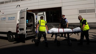 A body is taken on a stretcher after police shot the suspected terrorist.