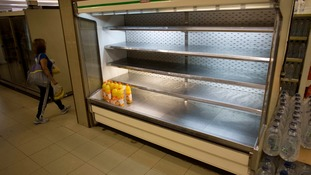 Supermarket shelves are empty in Venezuela as residents stockpile food.
