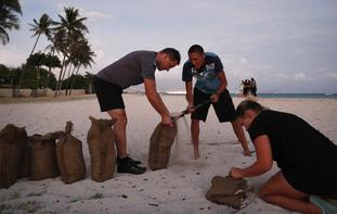 People fill up sandbags that will be used to help protect their homes