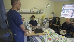 Young man on hospital bed with doctor and parents beside it