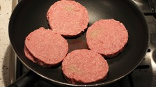 A general view of burgers in a pan.
