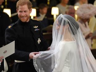 Prince Harry lifts Meghan Markle's veil at their wedding.