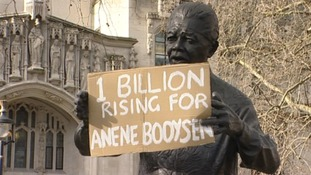 A sign is put in to the hands of the Parliament Square Nelson Mandela statue