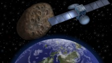 Artist's impression shows how the 'near-miss' asteroid might look passing in-between Earth and its communication satellites