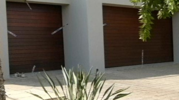 Broken police seals over the garage doors of the sports star's home