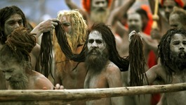 "Naga Sadhus hold the hair of another Naga Sadhu on the banks of the Ganges  at the ongoing ""Kumbh Mela"""