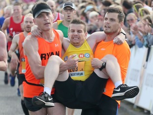 A runner is carried by other runners during the 2018 Simply Health Great North Run.