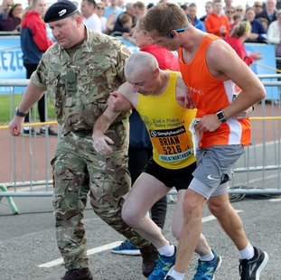 A runner is helped after crossing the finish line during the 2018 Simply Health Great North Run.