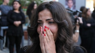 A colleague reacts as the coffin of Lebanese television cameraman Ali Shaaban of Al Jadeed TV.