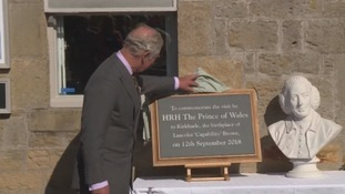 The prince unveils a plaque in Kirkharle.