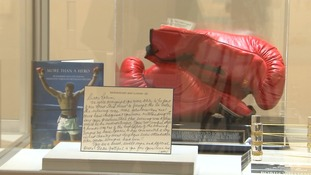 The items include boxing gloves and note from Muhammad Ali.