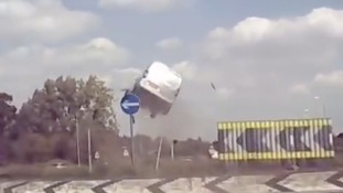 A screenshot from the video shows the van in mid-air above the roundabout.