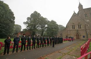 Emergency services personnel line up outside St Paul's Church