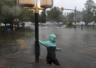 Someone wades through floodwater