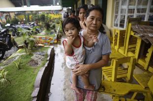 Evacuees walk inside an evacuation centre