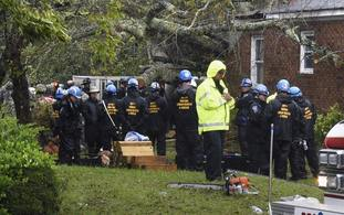 Rescue workers, police and fire department members wait to remove the bodies of a mother and child who were killed by a falling tree