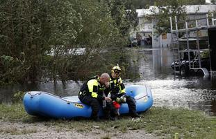 Rescuers search for people stranded by floodwaters