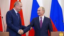 Recep Tayyip Erdogan and Vladimir Putin shake hands.