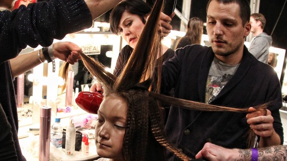 A model gets her hair prepared before the Marios Schwab Autumn/Winter London Fashion Week 2013 catwalk show