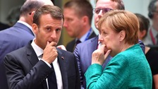 French president Emmanuel Macron and German chancellor Angela Merkel in deep conversation.