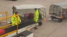 Baggage handler caught on video throwing people's luggage