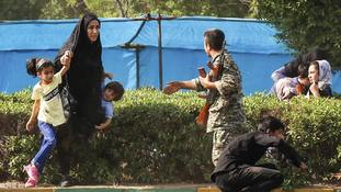 A woman takes her children to shelter as an army member tries to help them during a shooting at the military parade.