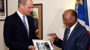 Prince William presents Namibia's Vice-President Nangolo Mbumba with a photo of his grandmother, Queen Elizabeth.