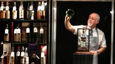 Danny McIlwraith from Bonhams cleans the cabinet which houses the whisky.