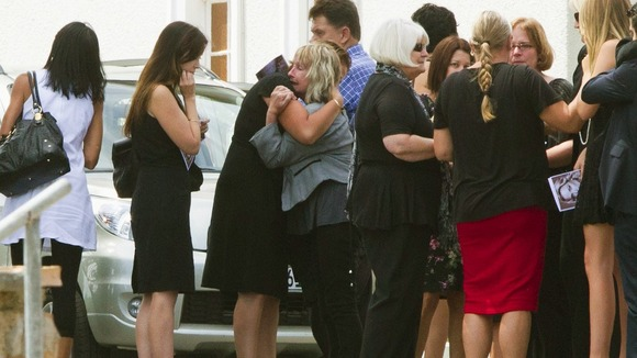 June Steenkamp (C, in grey) is comforted after the memorial service for her daughter