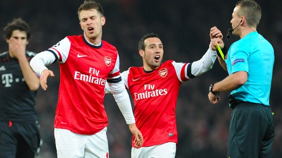 Aaron Ramsey and Santi Cazorla remonstrate with referee Svein Oddvar Moen