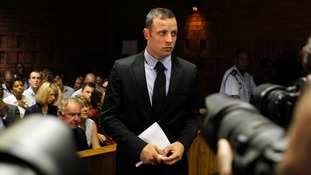 Photographers take pictures of Oscar Pistorius during a break in court proceedings