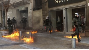 Riot police run by closed shops after protesters threw a petrol bomb