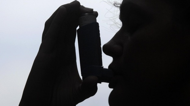 Patient using an inhaler to treat asthma