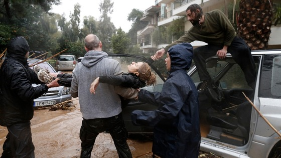 A woman is pulled to safety in Athens today.