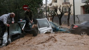 A woman stuck in her car is rescued from flood waters by residents in the Greek capital.