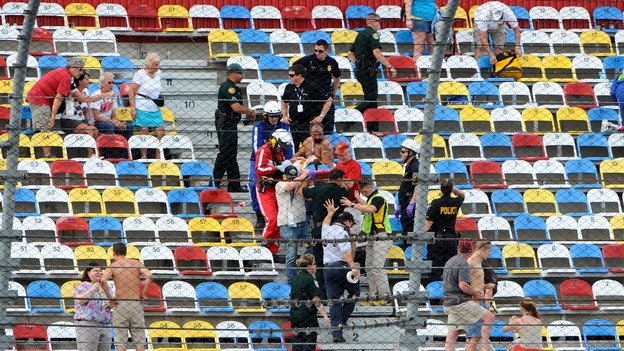 Emergency workers carry a fan from the Daytona circuit stands